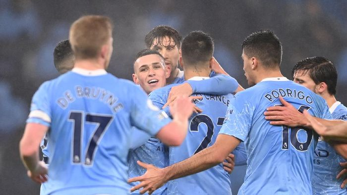 MANCHESTER, ENGLAND - JANUARY 13: Phil Foden of Manchester City is congratulated by teammates John Stones and Joao Cancelo after scoring their teams first goal during the Premier League match between Manchester City and Brighton & Hove Albion at Etihad Stadium on January 13, 2021 in Manchester, England. Sporting stadiums around England remain under strict restrictions due to the Coronavirus Pandemic as Government social distancing laws prohibit fans inside venues resulting in games being played behind closed doors. (Photo by Laurence Griffiths/Getty Images)