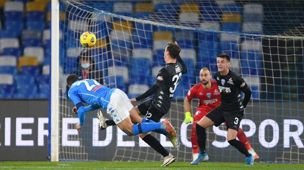 NAPLES, ITALY - JANUARY 13: Giovanni Di Lorenzo of Napoli scores their team's first goal as Nicolas Haas of Empoli attempts to block during the Coppa Italia match between SSC Napoli and Empoli FC at Stadio Diego Armando Maradona on January 13, 2021 in Naples, Italy. Sporting stadiums around Italy remain under strict restrictions due to the Coronavirus Pandemic as Government social distancing laws prohibit fans inside venues resulting in games being played behind closed doors. (Photo by Francesco Pecoraro/Getty Images)
