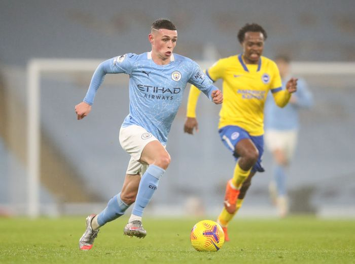 MANCHESTER, ENGLAND - JANUARY 13: Phil Foden of Manchester City makes a break during the Premier League match between Manchester City and Brighton & Hove Albion at Etihad Stadium on January 13, 2021 in Manchester, England. Sporting stadiums around England remain under strict restrictions due to the Coronavirus Pandemic as Government social distancing laws prohibit fans inside venues resulting in games being played behind closed doors. (Photo by Clive Brunskill/Getty Images)