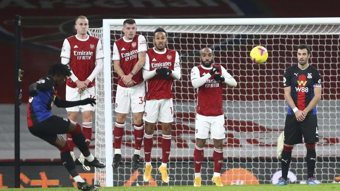 Crystal Palaces Eberechi Eze, left, ktakes a free kick during the English Premier League soccer match between Arsenal and Crystal Palace at Emirates Stadium in London, Thursday, Jan. 14, 2021. (Julian Finney/Pool via AP)