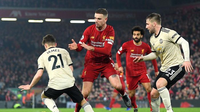LIVERPOOL, ENGLAND - JANUARY 19: Jordan Henderson of Liverpool battles for possession with Daniel James and Luke Shaw of Manchester United during the Premier League match between Liverpool FC and Manchester United at Anfield on January 19, 2020 in Liverpool, United Kingdom. (Photo by Michael Regan/Getty Images)