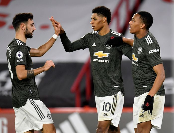 SHEFFIELD, ENGLAND - DECEMBER 17: Marcus Rashford of Manchester United celebrates with team mates (l - r) Bruno Fernandes and Anthony Martial after scoring their sides third goal  during the Premier League match between Sheffield United and Manchester United at Bramall Lane on December 17, 2020 in Sheffield, England. The match will be played without fans, behind closed doors as a Covid-19 precaution.  (Photo by Peter Powell - Pool/Getty Images)