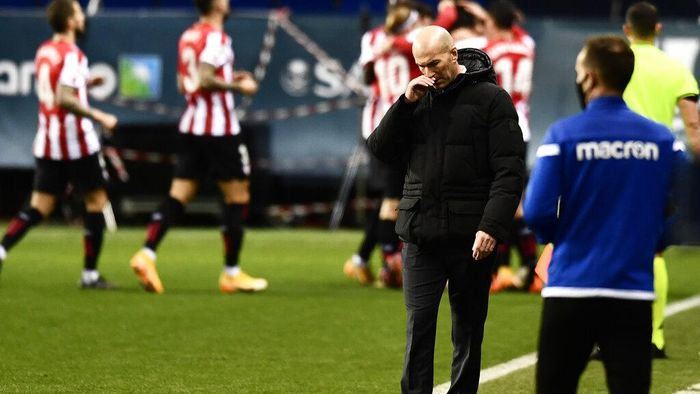 Real Madrids head coach Zinedine Zidane gestures as Athletic Bilbao players, background, celebrate their first goal during Spanish Super Cup semi final soccer match between Real Madrid and Athletic Bilbao at La Rosaleda stadium in Malaga, Spain, Thursday, Jan. 14, 2021. (AP Photo/Jose Breton)