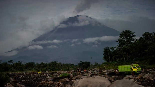 Mount Semeru looms over the village of Lumajang, East Java on January 17, 2021 after an eruption a day before. (Photo by Juni Kriswanto / AFP)