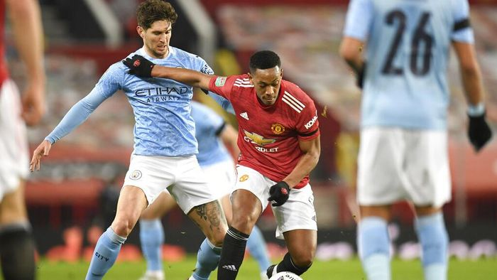 Manchester Citys John Stones, left, and Manchester Uniteds Anthony Martial fight for the ball during the English League Cup semifinal soccer match between Manchester United and Manchester City at Old Trafford in Manchester, England, Wednesday, Jan. 6, 2021. (Peter Powell/Pool via AP)