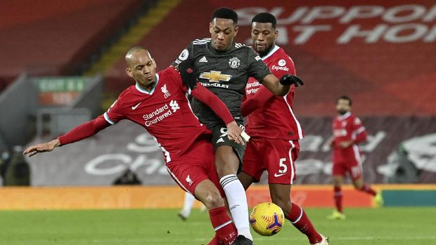 Manchester United's Anthony Martial fights for the ball with Liverpool's Fabinho, left, during the English Premier League soccer match between Liverpool and Manchester United at Anfield Stadium, Liverpool, England, Sunday, Jan. 17, 2021. (Paul Ellis/Pool via AP)