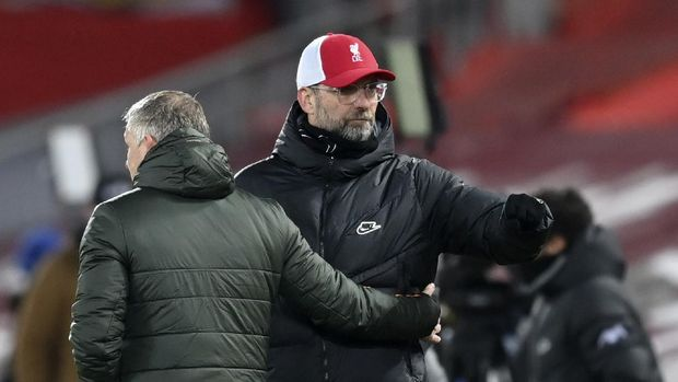 Liverpool's manager Jurgen Klopp, right, and Manchester United's manager Ole Gunnar Solskjaer greet each other at the end of the English Premier League soccer match between Liverpool and Manchester United at Anfield Stadium, Liverpool, England, Sunday, Jan. 17, 2021.(Michael Regan/Pool via AP)