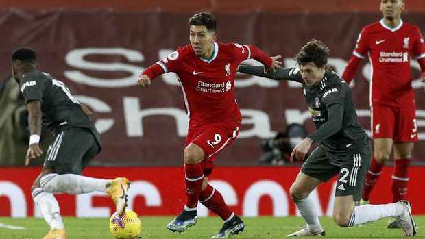 Liverpool's Roberto Firmino runs with the ball during the English Premier League soccer match between Liverpool and Manchester United at Anfield Stadium, Liverpool, England, Sunday, Jan. 17, 2021. (Phil Noble/Pool via AP)
