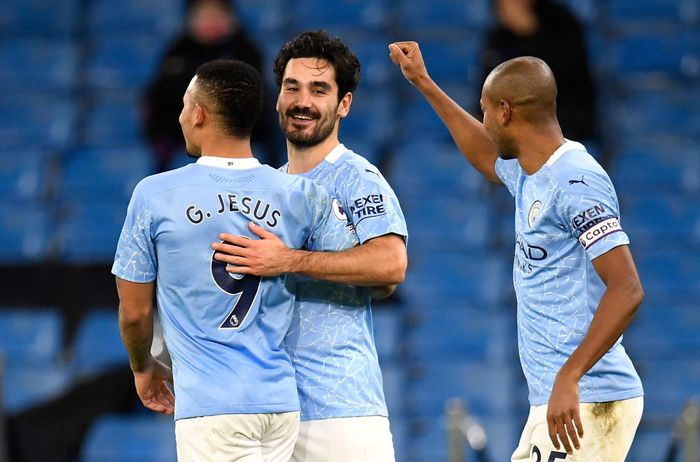 MANCHESTER, ENGLAND - JANUARY 17: Ilkay Gundogan of Manchester City celebrates with team mates (L - R) Gabriel Jesus and Fernandinho after scoring their sides second goal during the Premier League match between Manchester City and Crystal Palace at Etihad Stadium on January 17, 2021 in Manchester, England. Sporting stadiums around England remain under strict restrictions due to the Coronavirus Pandemic as Government social distancing laws prohibit fans inside venues resulting in games being played behind closed doors. (Photo by Peter Powell - Pool/Getty Images)