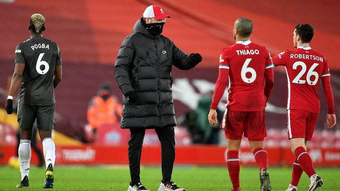 LIVERPOOL, ENGLAND - JANUARY 17: Jurgen Klopp, Manager of Liverpool interacts with Andrew Robertson after the Premier League match between Liverpool and Manchester United at Anfield on January 17, 2021 in Liverpool, England. Sporting stadiums around England remain under strict restrictions due to the Coronavirus Pandemic as Government social distancing laws prohibit fans inside venues resulting in games being played behind closed doors. (Photo by Paul Ellis - Pool/Getty Images)