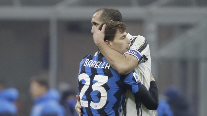 Inter Milans Nicolo Barella (23) embraces Juventus Giorgio Chiellini at the end of a Serie A soccer match between Inter Milan and Juventus at the San Siro stadium in Milan, Italy, Sunday, Jan. 17, 2021. (AP Photo/Luca Bruno)