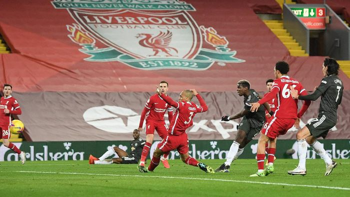 LIVERPOOL, ENGLAND - JANUARY 17: Paul Pogba of Manchester United has a shot saved whilst under pressure from Fabinho of Liverpool during the Premier League match between Liverpool and Manchester United at Anfield on January 17, 2021 in Liverpool, England. Sporting stadiums around England remain under strict restrictions due to the Coronavirus Pandemic as Government social distancing laws prohibit fans inside venues resulting in games being played behind closed doors. (Photo by Michael Regan/Getty Images)