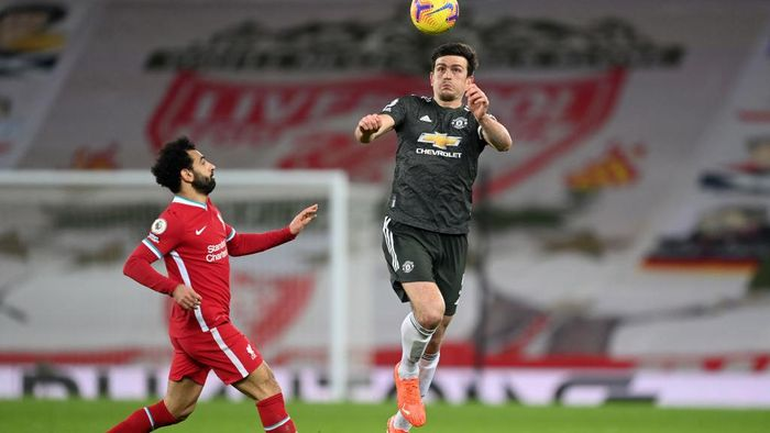 LIVERPOOL, ENGLAND - JANUARY 17: Harry Maguire of Manchester United heads the ball whilst under pressure from Mohamed Salah of Liverpool during the Premier League match between Liverpool and Manchester United at Anfield on January 17, 2021 in Liverpool, England. Sporting stadiums around England remain under strict restrictions due to the Coronavirus Pandemic as Government social distancing laws prohibit fans inside venues resulting in games being played behind closed doors. (Photo by Michael Regan/Getty Images)