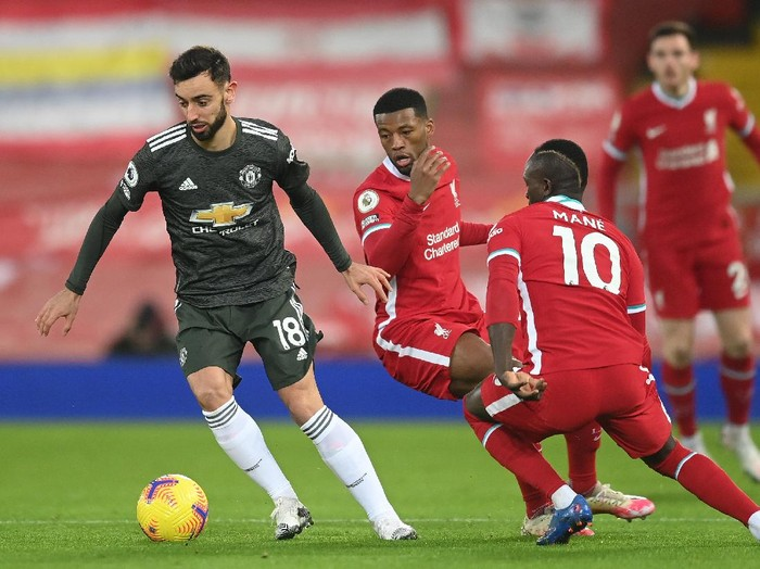 LIVERPOOL, ENGLAND - JANUARY 17: (L - R) Bruno Fernandes of Manchester United is challenged by Georginio Wijnaldum and Sadio Mane of Liverpool during the Premier League match between Liverpool and Manchester United at Anfield on January 17, 2021 in Liverpool, England. Sporting stadiums around England remain under strict restrictions due to the Coronavirus Pandemic as Government social distancing laws prohibit fans inside venues resulting in games being played behind closed doors. (Photo by Michael Regan/Getty Images)