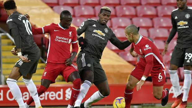 Manchester United's Paul Pogba, center, vies for the ball with Liverpool's Sadio Mane and Thiago, 2nd right, during the English Premier League soccer match between Liverpool and Manchester United at Anfield Stadium, Liverpool, England, Sunday, Jan. 17, 2021. (Paul Ellis/Pool via AP)