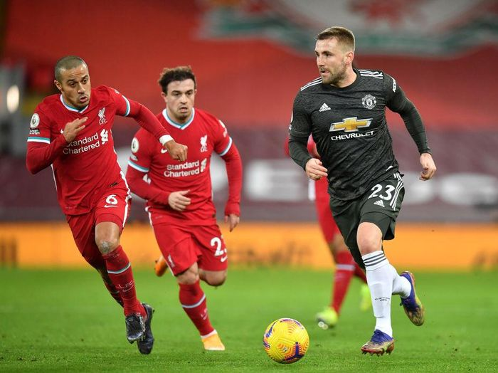 LIVERPOOL, ENGLAND - JANUARY 17: Luke Shaw of Manchester United runs with the ball whilst being closed down by Thiago Alcantara of Liverpool during the Premier League match between Liverpool and Manchester United at Anfield on January 17, 2021 in Liverpool, England. Sporting stadiums around England remain under strict restrictions due to the Coronavirus Pandemic as Government social distancing laws prohibit fans inside venues resulting in games being played behind closed doors. (Photo by Paul Ellis - Pool/Getty Images)