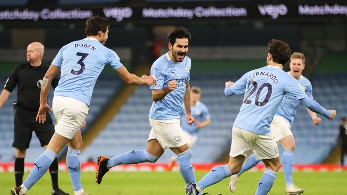 MANCHESTER, ENGLAND - JANUARY 17: Ilkay Gundogan of Manchester City celebrates with team mates (L - R) Ruben Dias and Bernardo Silva after scoring their sides second goal during the Premier League match between Manchester City and Crystal Palace at Etihad Stadium on January 17, 2021 in Manchester, England. Sporting stadiums around England remain under strict restrictions due to the Coronavirus Pandemic as Government social distancing laws prohibit fans inside venues resulting in games being played behind closed doors.  (Photo by Clive Brunskill/Getty Images)
