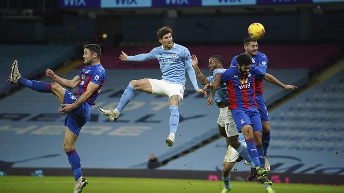 Manchester Citys John Stones, centre, heads the ball to score his sides opening goal during an English Premier League soccer match between Manchester City and Crystal Palace at the Etihad Stadium in Manchester, England, Sunday Jan.17, 2021. (AP Photo/Dave Thompson, Pool)