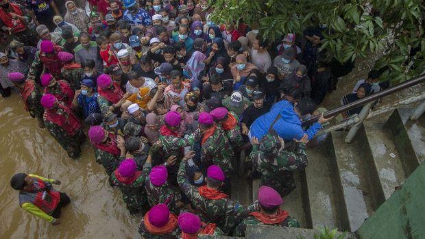 Warga antre untuk mendapatkan paket bantuan sembako Presiden Joko Widodo di Desa Pekauman Ulu, Kabupaten Banjar, Kalimantan Selatan, Senin (18/1/2021). Paket bantuan tersebut dibagikan langsung kepada warga yang menjadi korban banjir saat presiden meninjau bencana di Kalimantan Selatan tersebut. ANTARA FOTO/Bayu Pratama S/aww.