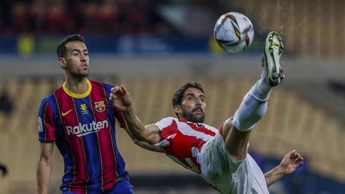 Athletic Bilbaos Raul Garcia, right, kicks the ball next to Barcelonas Sergio Busquets with during the Spanish Supercopa final soccer match between FC Barcelona and Athletic Bilbao at La Cartuja stadium in Seville, Spain, Sunday, Jan. 17, 2021. (AP Photo/Miguel Morenatti)