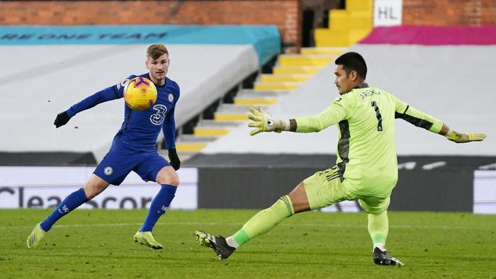 LONDON, ENGLAND - JANUARY 16: Timo Werner of Chelsea shoots past Alphonse Areola of Fulham during the Premier League match between Fulham and Chelsea at Craven Cottage on January 16, 2021 in London, England. Sporting stadiums around England remain under strict restrictions due to the Coronavirus Pandemic as Government social distancing laws prohibit fans inside venues resulting in games being played behind closed doors. (Photo by John Walton - Pool/Getty Images)