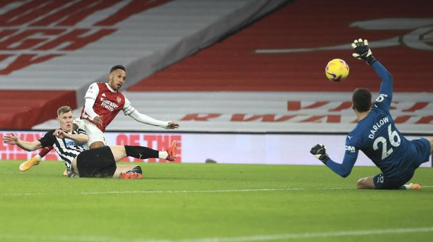 Arsenal's Pierre-Emerick Aubameyang scores his side's opening goal during the English Premier League soccer match between Arsenal and Newcastle United at Emirates Stadium in London, England, Monday, Jan.18, 2021. (Adam Davy/Pool via AP)