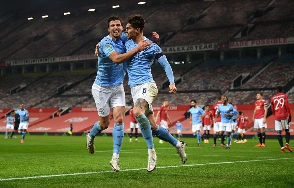 MANCHESTER, ENGLAND - JANUARY 06: John Stones of Manchester City celebrates at the final whistle with Ruben Dias of Manchester City during the Carabao Cup Semi Final match between Manchester United and Manchester City at Old Trafford on January 06, 2021 in Manchester, England. The match will be played without fans, behind closed doors as a Covid-19 precaution. (Photo by Peter Powell - Pool/Getty Images)