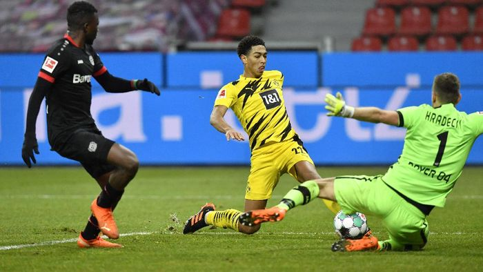 Dortmunds Jude Bellingham takes a shot at goal next to Leverkusens goalkeeper Lukas Hradecky during the German Bundesliga soccer match between Bayer Leverkusen and Borussia Dortmund in Leverkusen, Germany, Tuesday, Jan. 19, 2021. (AP Photo/Martin Meissner, Pool)