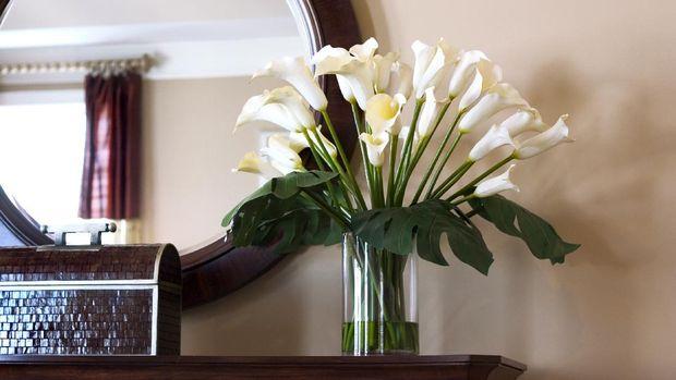 calla lilies near mirror on a dresser