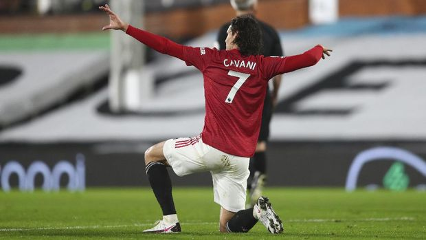 Manchester United's Edinson Cavani celebrates after scoring his side's opening goal during the English Premier League soccer match between Fulham and Manchester United at the Craven Cottage stadium in London, Wednesday, Jan. 20, 2021. (Clive Rose/Pool via AP)