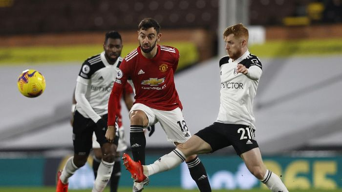 LONDON, ENGLAND - JANUARY 20: Bruno Fernandes of Manchester United battles for possession with Harrison Reed of Fulham  during the Premier League match between Fulham and Manchester United at Craven Cottage on January 20, 2021 in London, England. Sporting stadiums around the UK remain under strict restrictions due to the Coronavirus Pandemic as Government social distancing laws prohibit fans inside venues resulting in games being played behind closed doors. (Photo by Adrian Dennis - Pool/Getty Images)