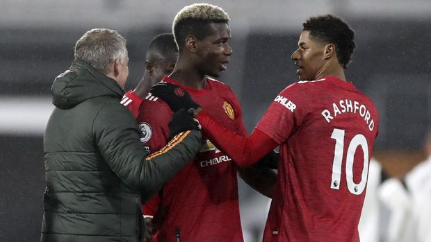 Manchester United's Paul Pogba, centre, celebrates with Manchester United's manager Ole Gunnar Solskjaer, left, and Manchester United's Marcus Rashford at the end of the English Premier League soccer match between Fulham and Manchester United at the Craven Cottage stadium in London, Wednesday, Jan. 20, 2021. (Peter Cziborra/Pool via AP)