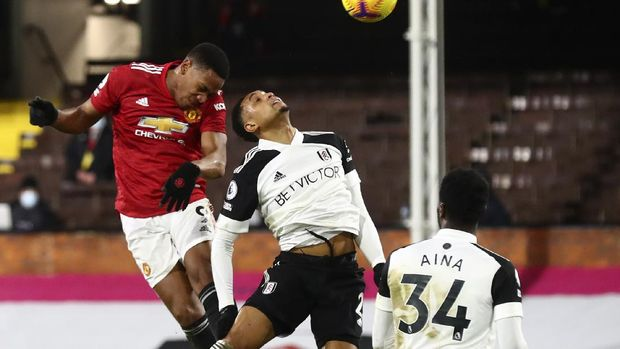 Manchester United's Anthony Martial, left, heads the ball during the English Premier League soccer match between Fulham and Manchester United at the Craven Cottage stadium in London, Wednesday, Jan. 20, 2021. (Clive Rose/Pool via AP)