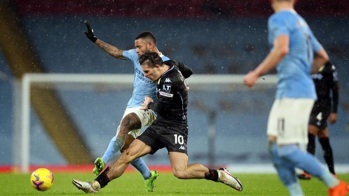 MANCHESTER, ENGLAND - JANUARY 20: Jack Grealish of Aston Villa and Gabriel Jesus of Manchester City battle for the ball  during the Premier League match between Manchester City and Aston Villa at Etihad Stadium on January 20, 2021 in Manchester, England. Sporting stadiums around the UK remain under strict restrictions due to the Coronavirus Pandemic as Government social distancing laws prohibit fans inside venues resulting in games being played behind closed doors. (Photo by Clive Brunskill/Getty Images)