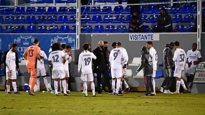 Real Madrids head coach Zinedine Zidane, centre speaks with his players as the Spanish Copa del Rey round of 32 soccer match between Alcoyano and Real Madrid goes into extra time at the El Collao stadium in Alcoy, Spain, Wednesday Jan. 20, 2021. (AP Photo/Jose Breton)