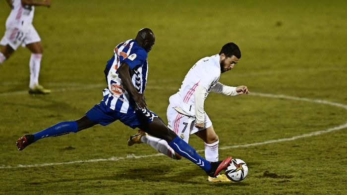 Alcoyanos Ali Diakite, left, challenges for the ball with Real Madrids Eden Hazard during a Spanish Copa del Rey round of 32 soccer match between Alcoyano and Real Madrid at the El Collao stadium in Alcoy, Spain, Wednesday Jan. 20, 2021. (AP Photo/Jose Breton)