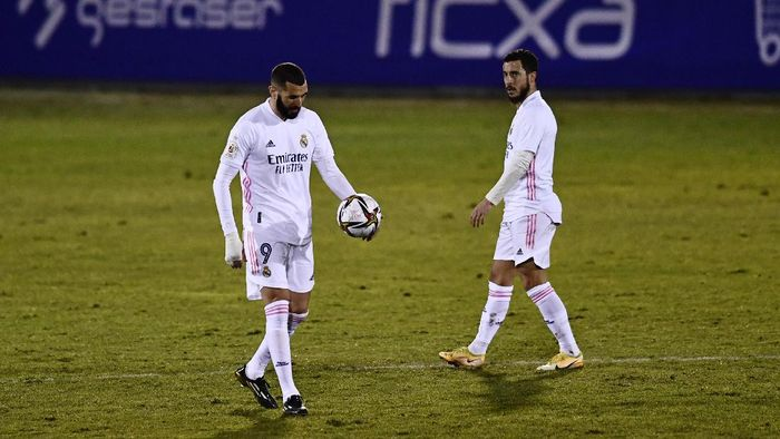 Real Madrids Karim Benzema walks with the ball watched by Eden Hazard after after Alcoyanos Juanan scored his sides second goal during a Spanish Copa del Rey round of 32 soccer match between Alcoyano and Real Madrid at the El Collao stadium in Alcoy, Spain, Wednesday Jan. 20, 2021. (AP Photo/Jose Breton)