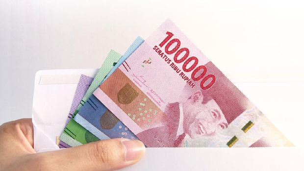 woman hand showing envelope and Indonesia rupiah money