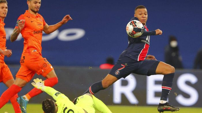 PSGs Kylian Mbappe, right, scores his sides opening goal during the French League One soccer match between Paris Saint-Germain and Montpellier at the Parc des Princes stadium in Paris, France, Friday, Jan.22, 2021. (AP Photo/Thibault Camus)