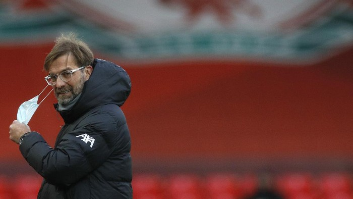 LIVERPOOL, ENGLAND - JANUARY 17: Jurgen Klopp, Manager of Liverpool removes his face mask ahead of being interviewed prior to kick off during the Premier League match between Liverpool and Manchester United at Anfield on January 17, 2021 in Liverpool, England. Sporting stadiums around England remain under strict restrictions due to the Coronavirus Pandemic as Government social distancing laws prohibit fans inside venues resulting in games being played behind closed doors. (Photo by Phil Noble - Pool/Getty Images)
