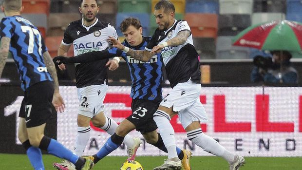 Udinese's Roberto Pereyra, right,  challenges Inter's Nicolo Barella during the Serie A soccer match between Udinese and Inter Milan, at the Dacia Arena in Udine, Italy, Saturday, Jan. 23, 2021. (Gianpaolo Scognamiglio/LaPresse via AP)