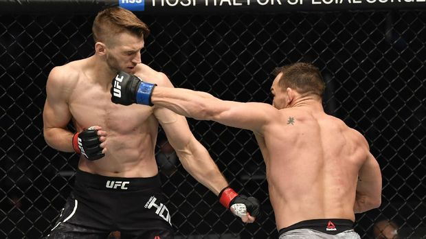 Jan 23, 2021; Abu Dhabi, United Arab Emirates; Michael Chandler punches Dan Hooker of New Zealand in a lightweight fight during the UFC 257 event inside Etihad Arena on UFC Fight Island.  Mandatory Credit: Jeff Bottari/Handout Photo via USA TODAY Sports