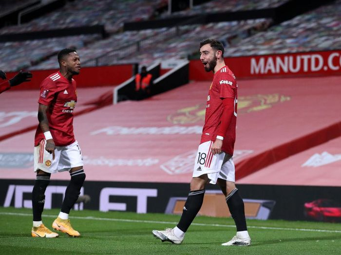 MANCHESTER, ENGLAND - JANUARY 24: Bruno Fernandes of Manchester United celebrates with team mate Fred (L) after scoring their sides third goal from a free kick during The Emirates FA Cup Fourth Round match between Manchester United and Liverpool at Old Trafford on January 24, 2021 in Manchester, England. Sporting stadiums around the UK remain under strict restrictions due to the Coronavirus Pandemic as Government social distancing laws prohibit fans inside venues resulting in games being played behind closed doors. (Photo by Martin Rickett - Pool/Getty Images)