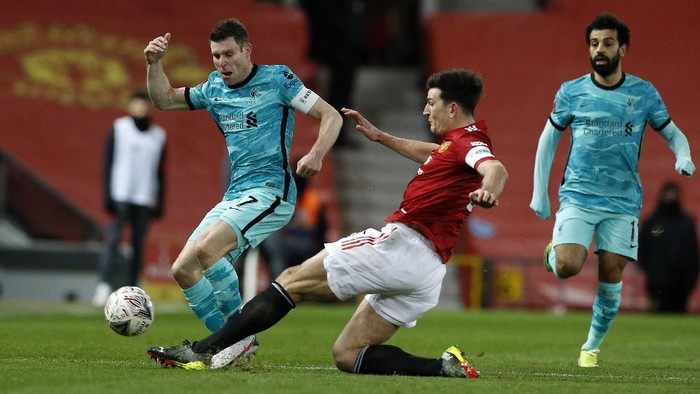 MANCHESTER, ENGLAND - JANUARY 24: James Milner of Liverpool is tackled by Harry Maguire of Manchester United during The Emirates FA Cup Fourth Round match between Manchester United and Liverpool at Old Trafford on January 24, 2021 in Manchester, England. Sporting stadiums around the UK remain under strict restrictions due to the Coronavirus Pandemic as Government social distancing laws prohibit fans inside venues resulting in games being played behind closed doors. (Photo by Phil Noble - Pool/Getty Images)