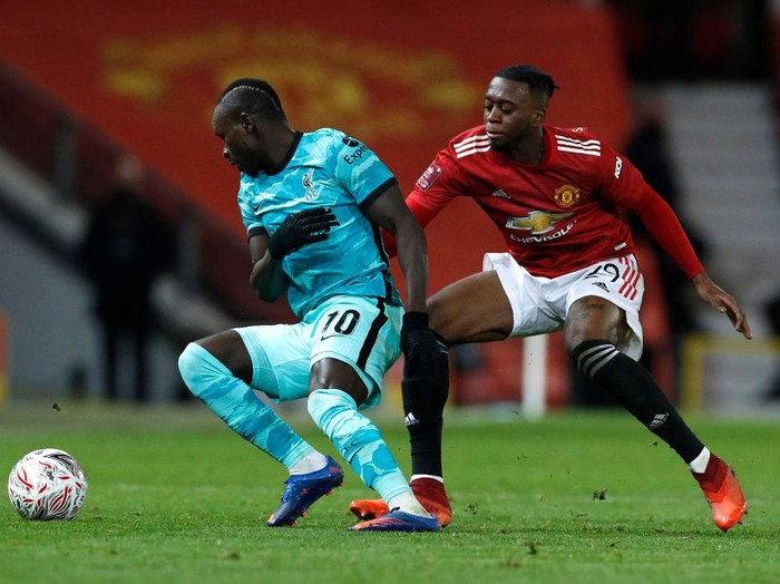 MANCHESTER, ENGLAND - JANUARY 24: Aaron Wan-Bissaka of Manchester United battles for possession with Sadio Mane of Liverpool during The Emirates FA Cup Fourth Round match between Manchester United and Liverpool at Old Trafford on January 24, 2021 in Manchester, England. Sporting stadiums around the UK remain under strict restrictions due to the Coronavirus Pandemic as Government social distancing laws prohibit fans inside venues resulting in games being played behind closed doors. (Photo by Phil Noble - Pool/Getty Images)