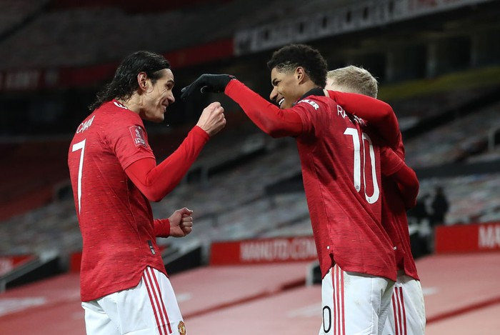 MANCHESTER, ENGLAND - JANUARY 24: Marcus Rashford of Manchester United is congratulated by team mates (L - R) Edinson Cavani and Donny Van De Beek after scoring their sides second goal during The Emirates FA Cup Fourth Round match between Manchester United and Liverpool at Old Trafford on January 24, 2021 in Manchester, England. Sporting stadiums around the UK remain under strict restrictions due to the Coronavirus Pandemic as Government social distancing laws prohibit fans inside venues resulting in games being played behind closed doors. (Photo by Martin Rickett - Pool/Getty Images)