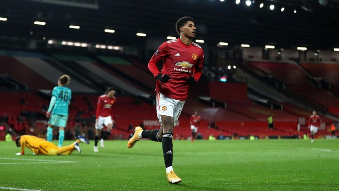 MANCHESTER, ENGLAND - JANUARY 24: Marcus Rashford of Manchester United celebrates after scoring their sides second goal during The Emirates FA Cup Fourth Round match between Manchester United and Liverpool at Old Trafford on January 24, 2021 in Manchester, England. Sporting stadiums around the UK remain under strict restrictions due to the Coronavirus Pandemic as Government social distancing laws prohibit fans inside venues resulting in games being played behind closed doors. (Photo by Martin Rickett - Pool/Getty Images)