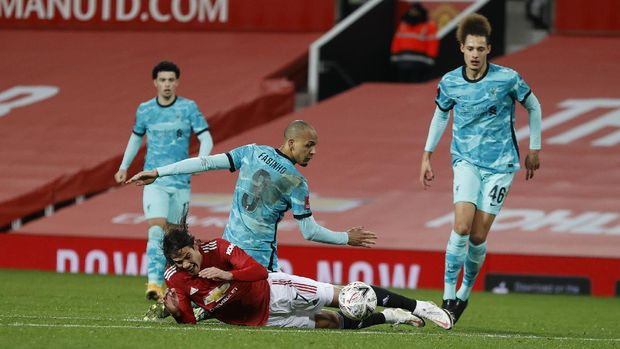 Manchester United's Edinson Cavani, falls to the ground fouled by Liverpool's Roberto Firmino during the English FA Cup 4th round soccer match between Manchester United and Liverpool at Old Trafford in Manchester, England, Sunday, Jan. 24, 2021. (Phil Noble/Pool via AP)