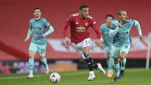 Manchester United's Mason Greenwood runs with the ball during the English FA Cup 4th round soccer match between Manchester United and Liverpool at Old Trafford in Manchester, England, Sunday, Jan. 24, 2021. (Laurence Griffiths/Pool via AP)