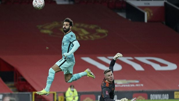 Liverpool's Mohamed Salah scores the opening goal past Manchester United's goalkeeper Dean Henderson during the English FA Cup 4th round soccer match between Manchester United and Liverpool at Old Trafford in Manchester, England, Sunday, Jan. 24, 2021. (Martin Rickett/Pool via AP)